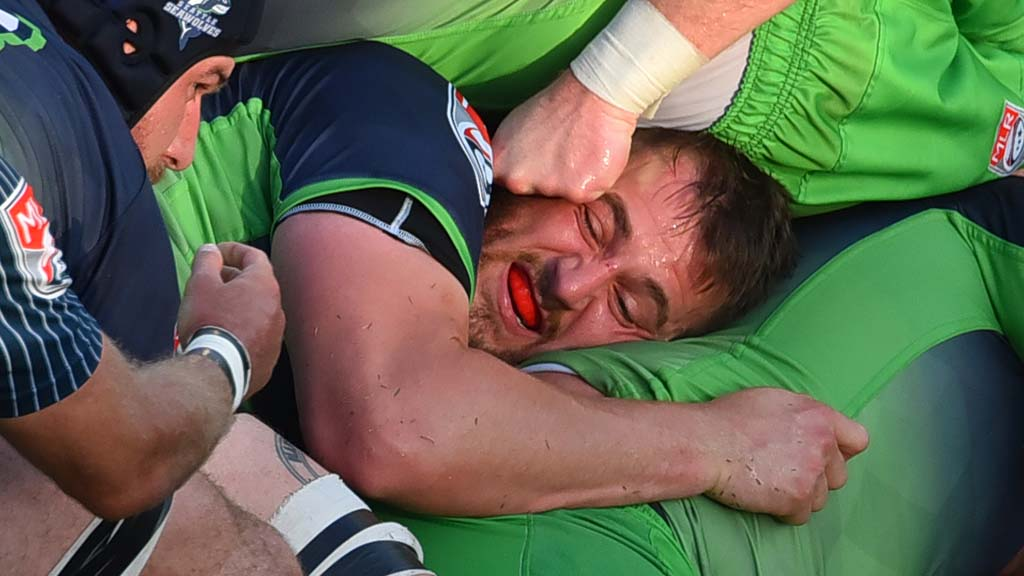 Tight in a scrum, a Seattle player holds onto his teammates and mouth guard.