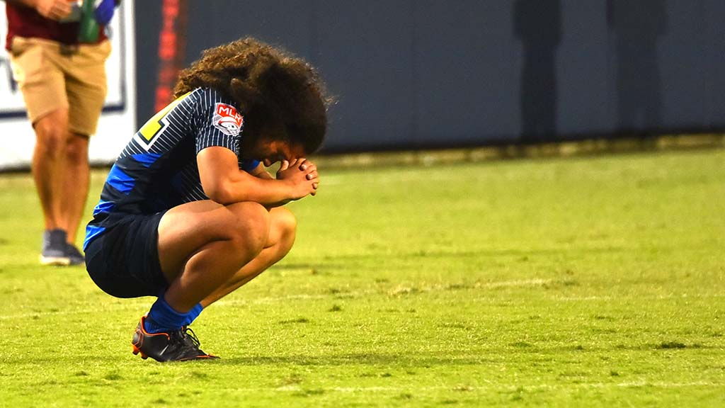 A Glendale player crouches in solitude after Seattle won the match.