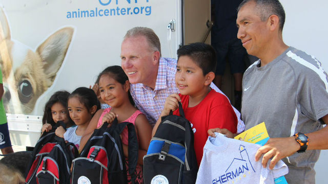 Mayor Kevin Faulconer with children who received backpacks