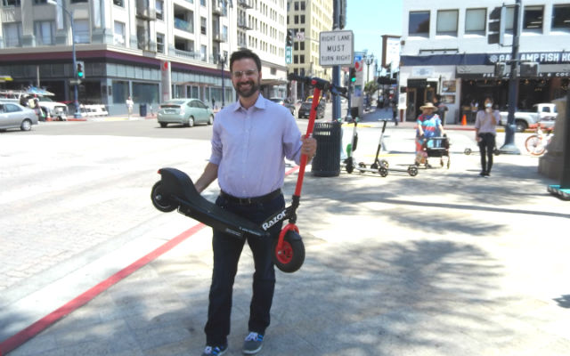 Danny Simon holds Razor electric scooter