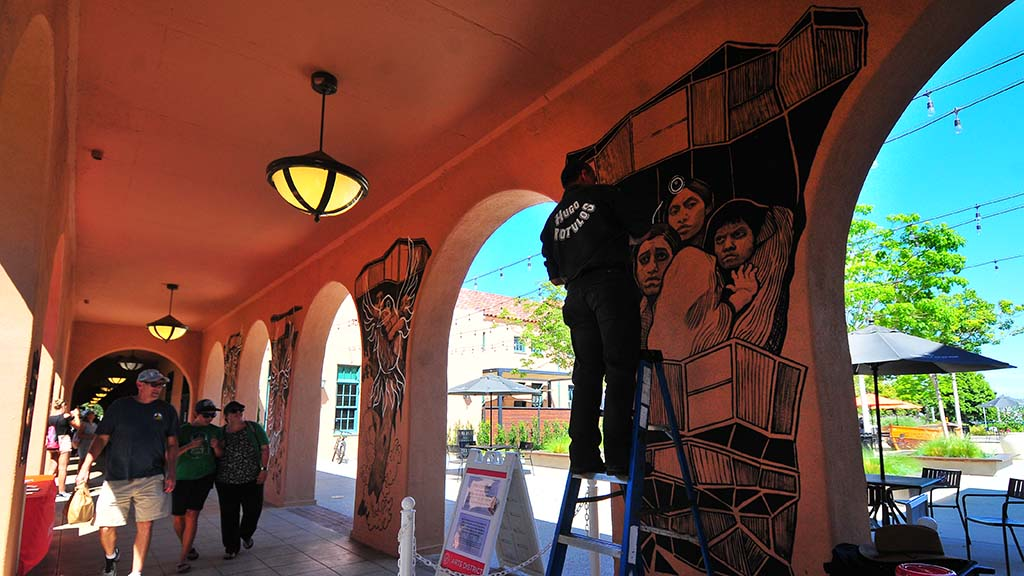 Visitors to Liberty Station pass as artist Hugo Crosthwaite paints a family on one of the columns at Barracks 14.