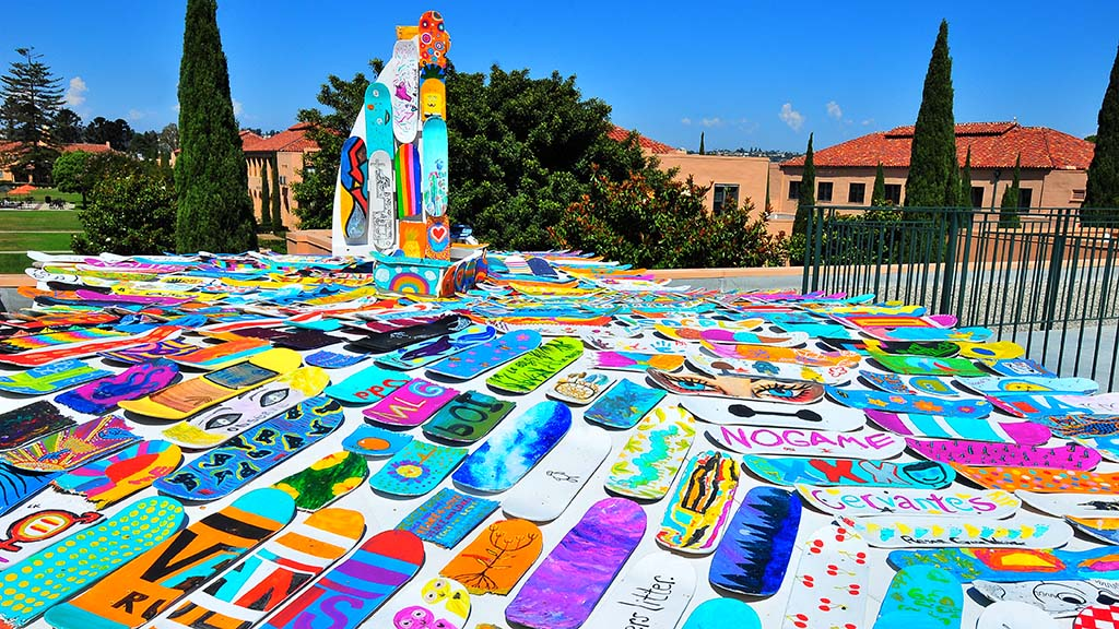 """Rolling it Forward"" on the roof of Building 202 represents a boat and rolling waves made entirely of community-painted skateboards."