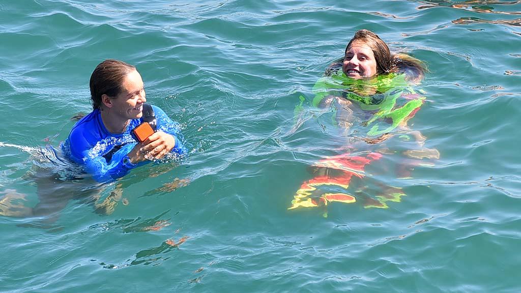 A lifeguard intern and junior lifeguard talk after a successful jump.