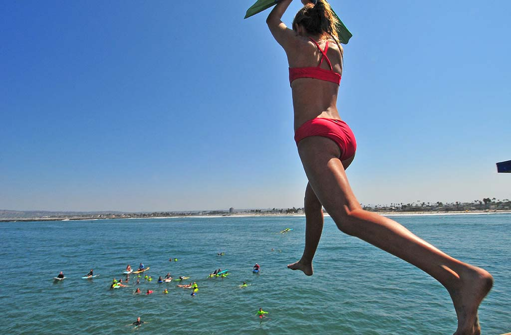 A young woman steps off to leap in the ocean.