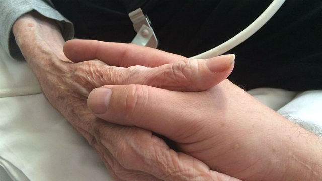 Seriously ill mother holding hands with son