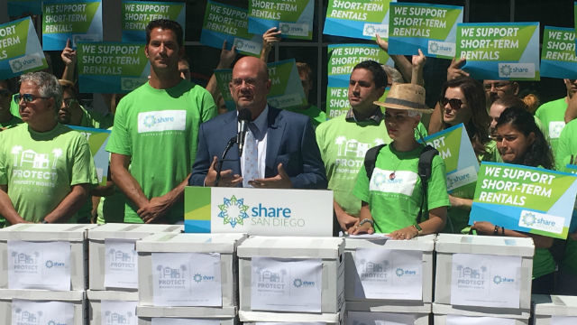Scott Sherman with vacation-rental supporters and boxes of petition signatures