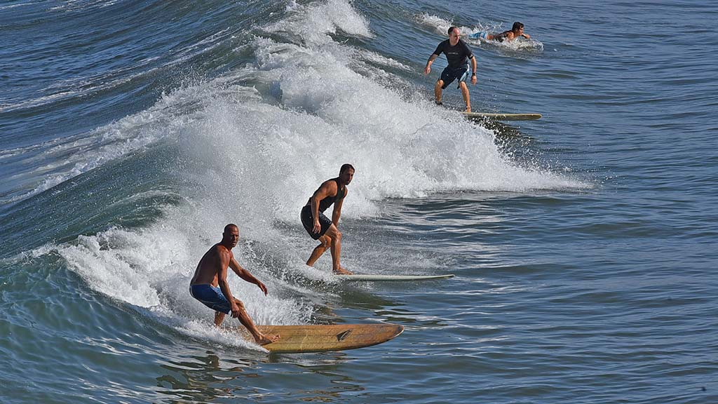 Surfers hit the waves on a cooler summer morning at Ocean Beach.