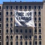 "Banner saying 'FREE OUR FAMILIES NOW"" was hanged from near top of Westin Gaslamp Hotel."