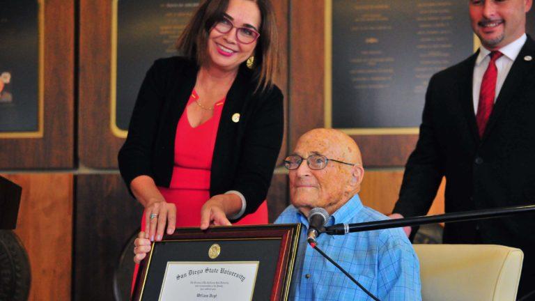 SDSU President Adela de la Torre presents 105-year-old Bill Vogt with his diploma.