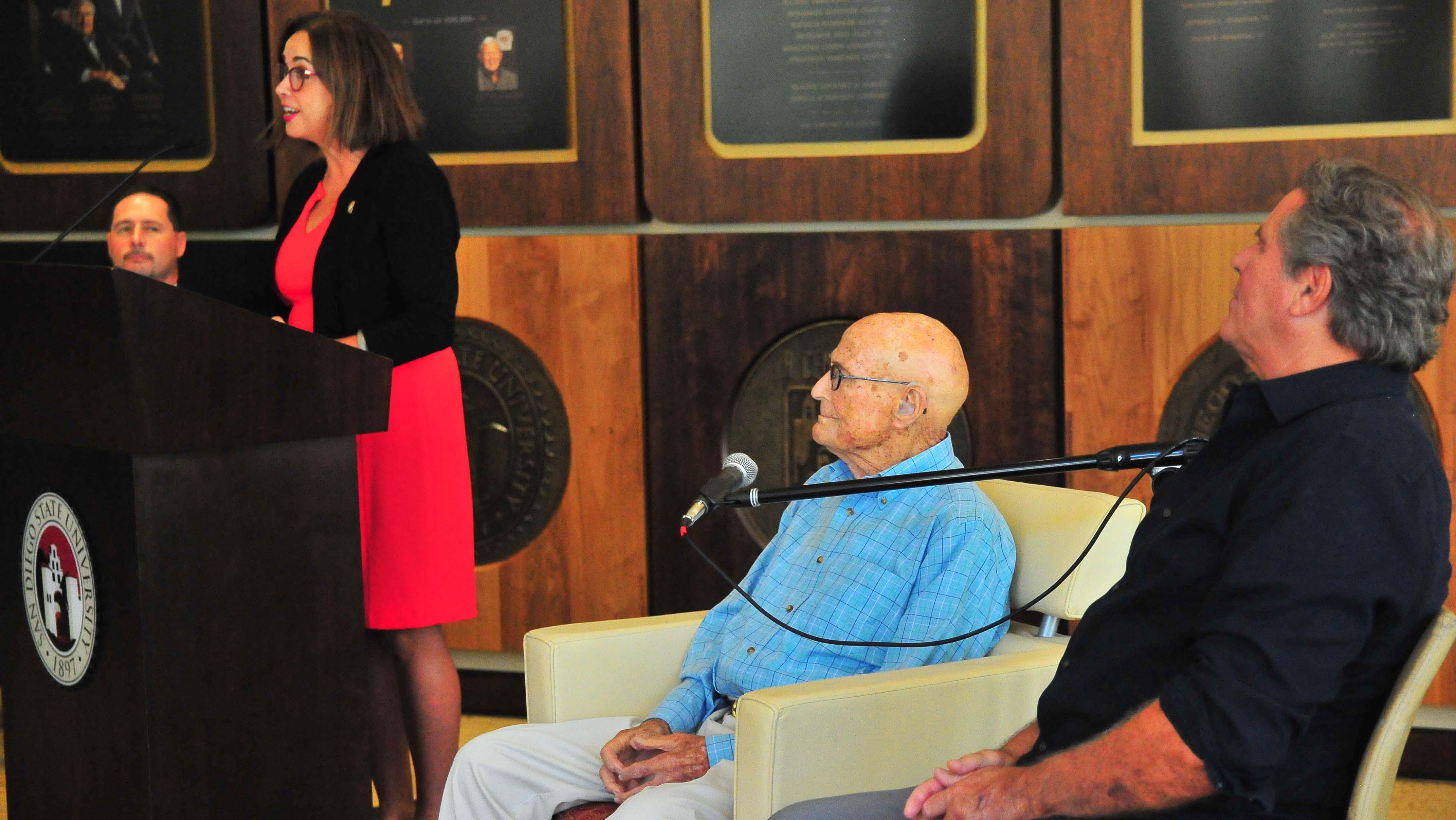 SDSU President Adela de la Torre praised Bill Vogt's dedication to SDSU. Vogt's son, Bob, sits beside him.