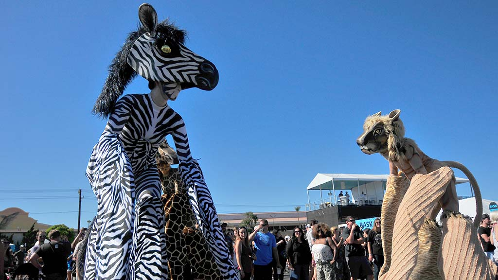 Puppet actors playing animals (on stilts) roam the Del Mar Fairgrounds crowds at KAABOO Del Mar.