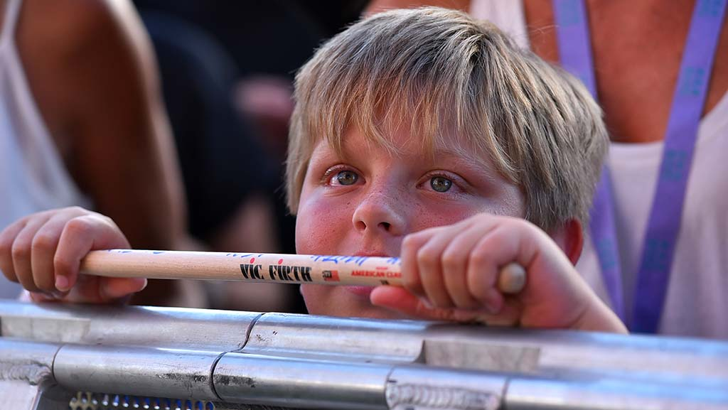 A boy watches Bill Idol as he holds a drum stick tossed into the crowd by the singer.