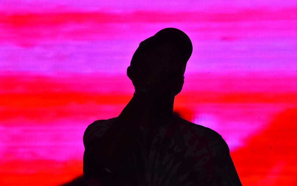 Pharrell Williams, lead vocalist for N.E.R.D. is silhouetted against a colorful screen.