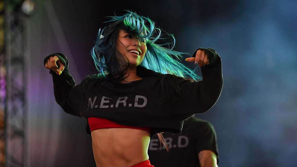 A dancer for N.E.R.F performs in front of a stage screen.