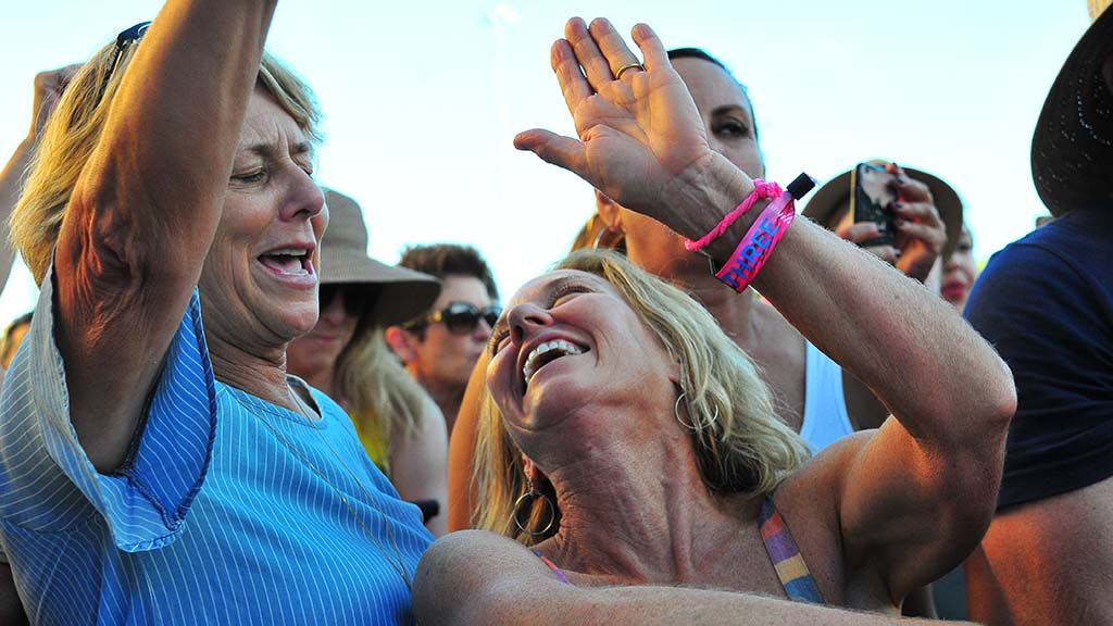 Fans of Melissa Etheridge share a moment in the front area of the audience.