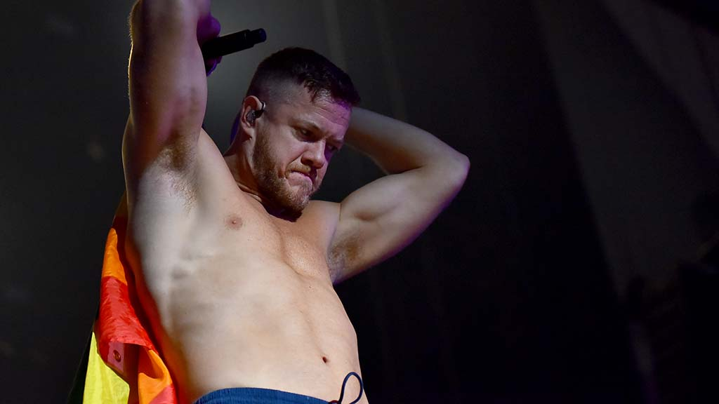 Dan Reynolds, lead singer for Imagine Dragon, begins to wrap rainbow flags around him during his KAABOO concert.