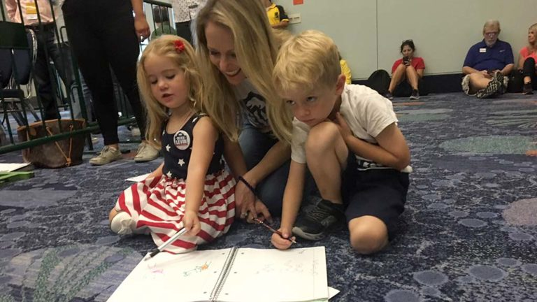 Chrissy Levin, wife of 49th Congressional District candidate Mike Levin, keeps her kids busy in back of Anaheim Convention Center ballroom awaiting arrival of President Obama.