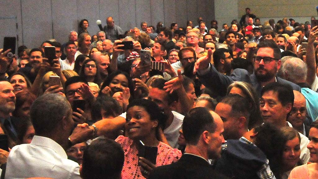 Crowd members stretch out their hands to shake hands with Obama at the end of the event.