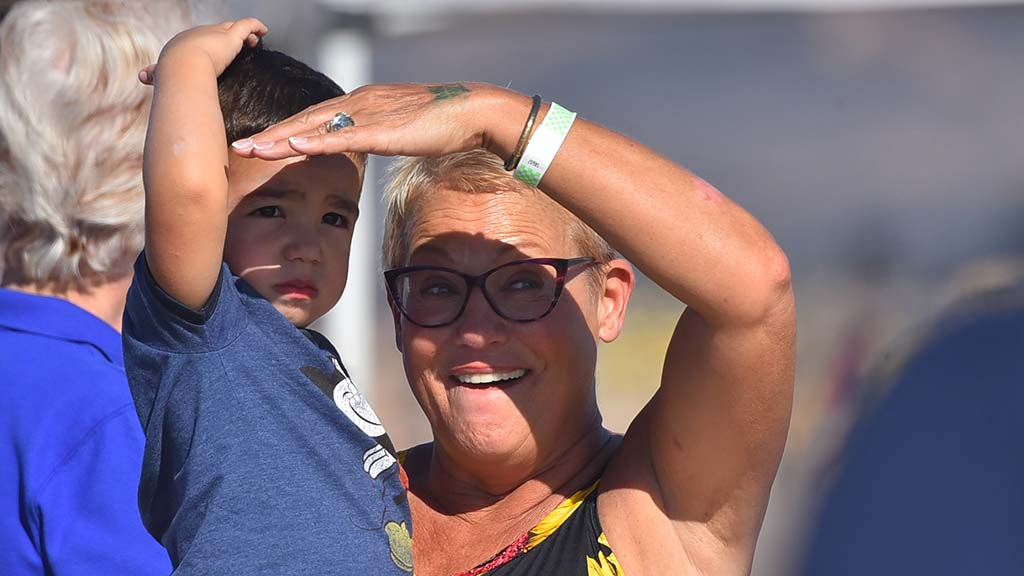 A woman shields her eyes and a boy's eyes from the afternoon sun at the 2018 Miramar Air Show.