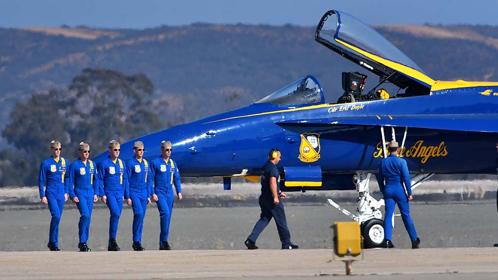 Blue Angel pilots walk to their planes prior to takeoff.