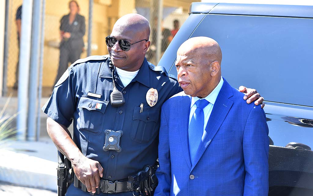 San Diego police availed themselves of photos with Rep. John Lewis before leaving Morse High School at noon.