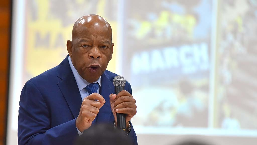 "Rep. John Lewis speaks in front of posters showing covers of his ""March"" trilogy of comic books."