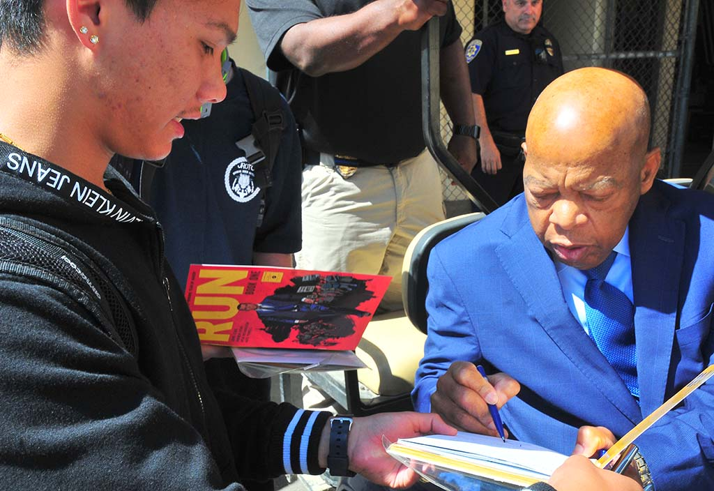 Rep. John Lewis signs autograph for a student as he prepares to leave gym area.