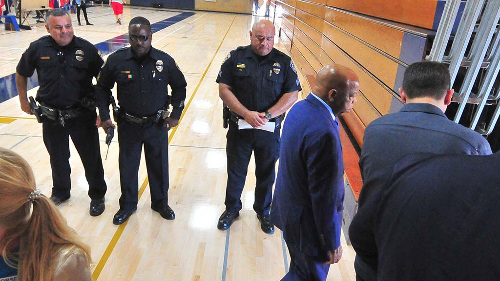 San Diego Unified School District police watch John Lewis leave after shaking his hand.