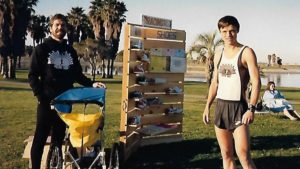 """Mission Bay Park image from about 1990 shows Carl Brandt with baby jogger. Rick Vandertie (right) wears a Movin' Shoes racing top. """"The wood-carved signs on the board were done by Dave Yarbrough, and I remember him carving those in the La Mesa store. ... The Nike track spikes on the boards hail from that time period as well."""""""