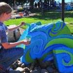 Daniela Davidoff, an SDSU intern, adds colors to a boulder near the creek