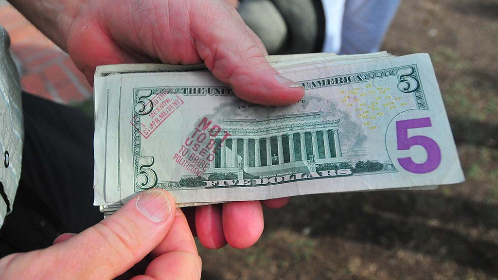 Ben Cohen show a bill stamped with his rubber stamps protesting big money in politics.