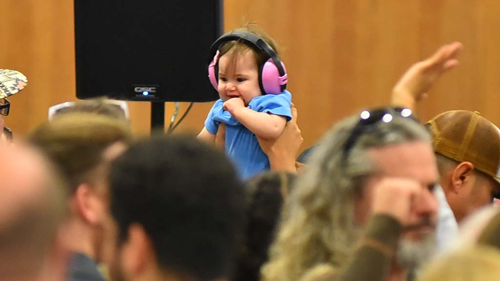 A little one has ear protection as a band plays rock music prior to candidate speeches.