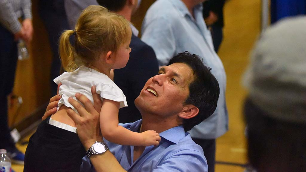 U.S. Senate candidate Kevin DeLeon plays with a child behind the rally stage.