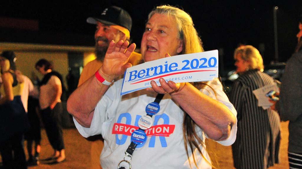 Madge Torres of Encinitas sells Bernie Sanders in 2020 bumper stickers after the rally in Oceanside.