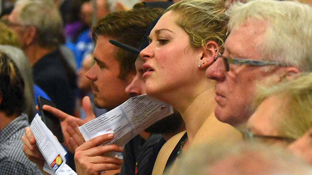 An attendee fans herself with a voter guide as candidates speak in a warm gym at MiraCosta College in Oceanside.
