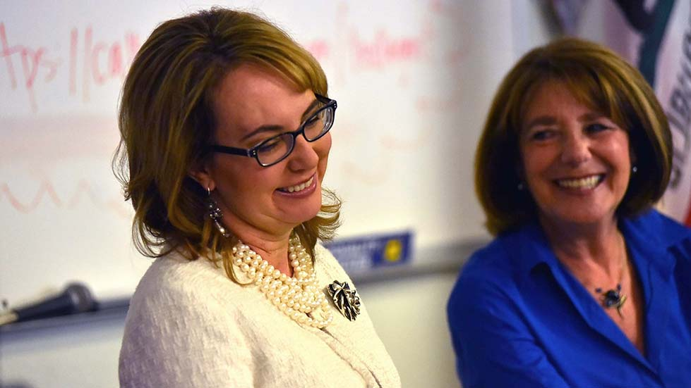 Former Rep. Gabriel Giffords smiles as Mike Levin talks about when she and her husband, Mark Kelly, met.