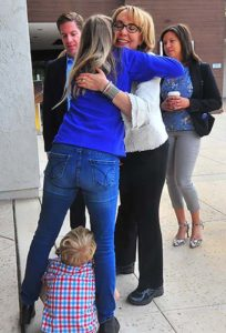 Former Rep. Gabrielle Giffords hugs Chrissy Levin as son Jonathon, 6, hides between his mother's legs.