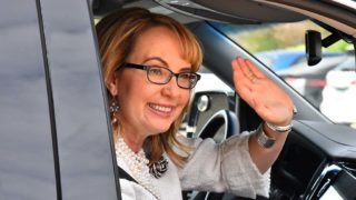 Former Rep. Gabriel Giffords waves goodbye to the Levin family as she leaves the gathering in Solana Beach.