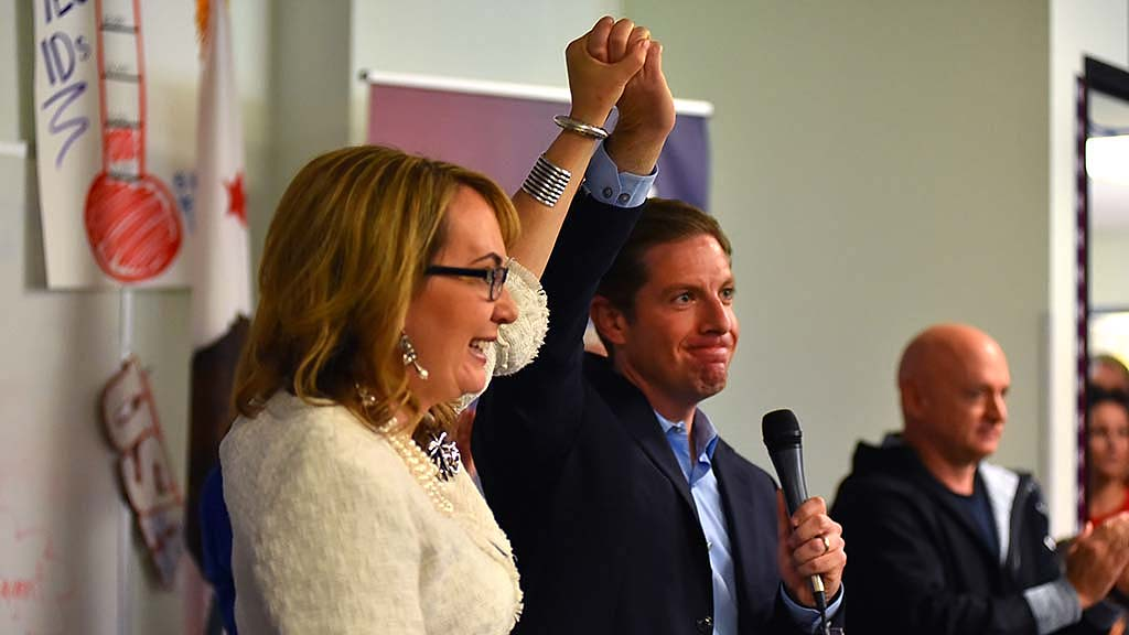Congressional candidate Mike Levin joins hands with former Rep. Gabriel Giffords when she visited his headquarters.
