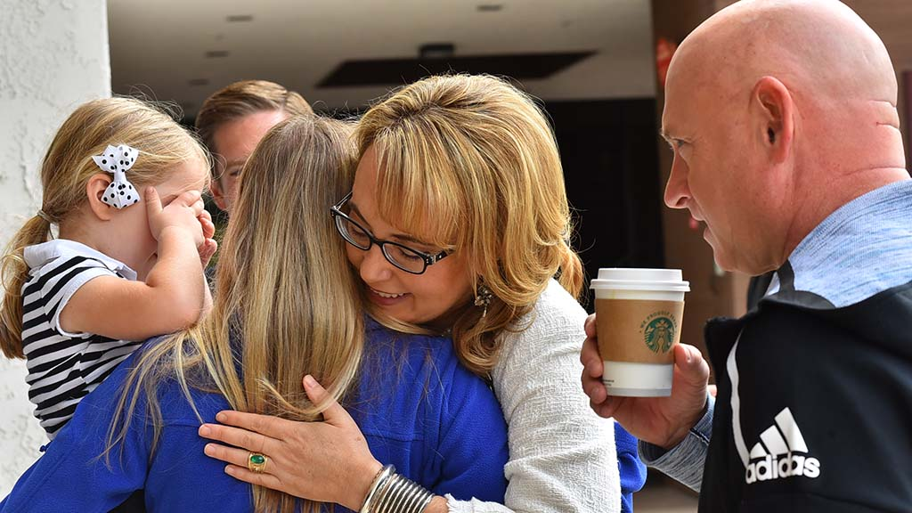 Former Rep. Gabriel Giffords hugs Mike Levin's wife, Chrissy, as daughter, Elizabeth, 4, plays shy.