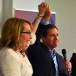 Mike Levin holds hands aloft with former Rep. Gabby Giffords with her husband Mark Kelly in background