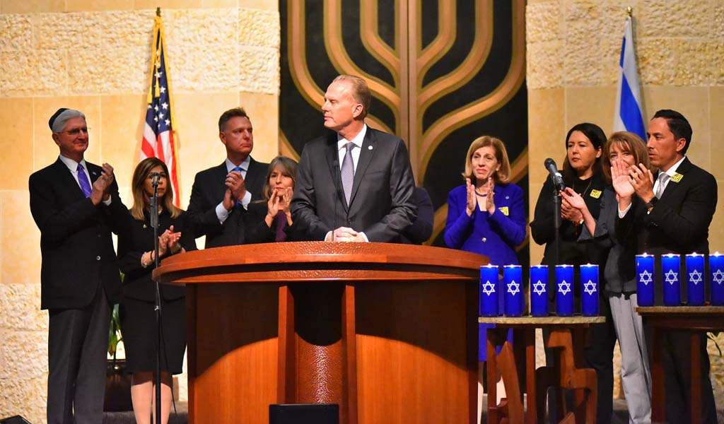 "San Diego Mayor Kevin Faulconer is applauded on the bima after saying: ""Anti-Semitism, racism and bigotry not only is unacceptable, it is profoundly un-American."""