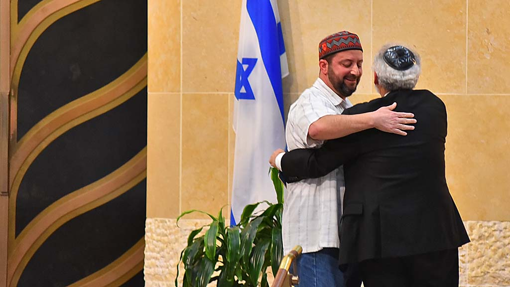 Rabbi Michael Berk of Beth Israel gives Imam Taha Hassane a hug at vigil.