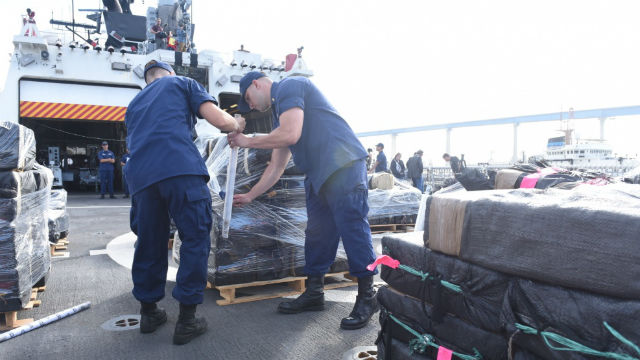 Coast Guard personnel with bundles of cocaine