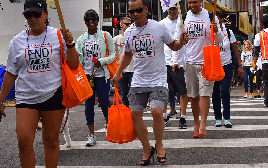 Tee Udompan of North Park (center) gingerly walks across an intersection as the black stilettos start to take a toll on his feet.