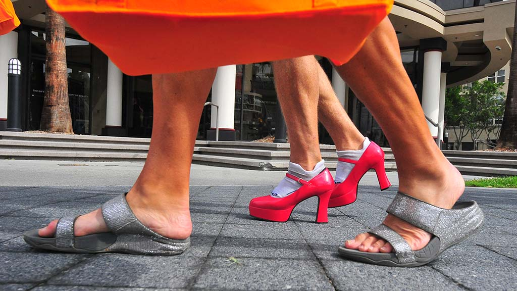 Men choose between flats and high heels from the boxes of shoes lended to the men.