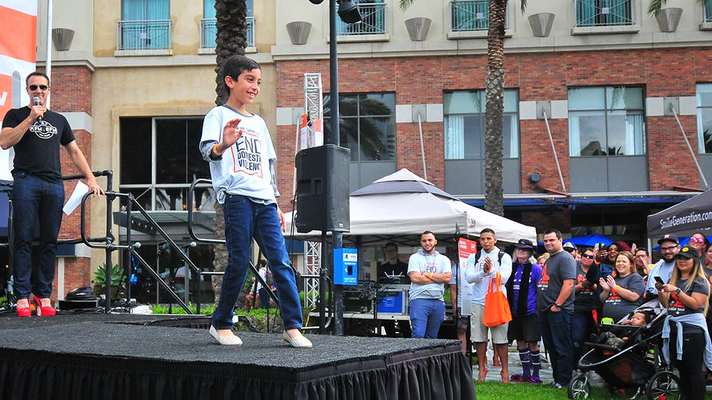 Alex Alcaraz, 8, shows off his sparkly shoes that match his mother's for the walk.
