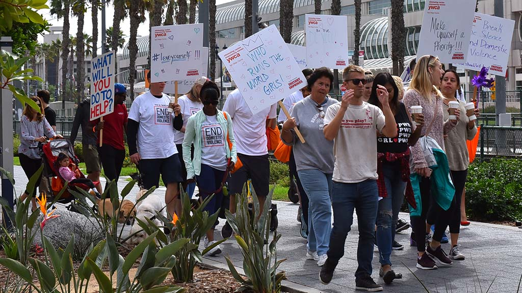 More than one hundred people, some carrying signs advocating for domestic violence victims, participated in the fundraiser for the YWCA.