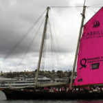 The yacht America with a pink mainsail