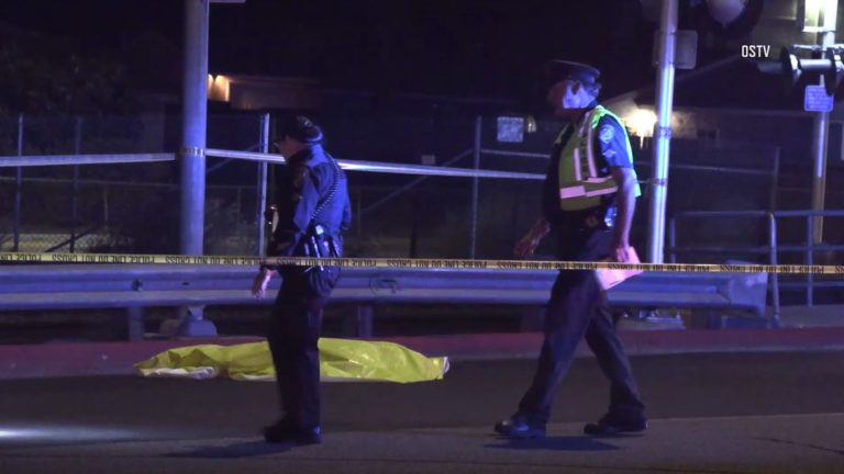 Police officers search for evidence near victim's body